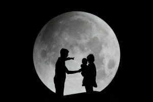 Silhouette of family with moon