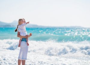 Mother on sea shore with baby pointing on copy space