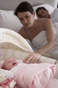 Newborn Baby Crying In Cot In Parents Bedroom