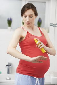 Pregnant Woman Spraying Mosquito Repellant To Protect Against Zi